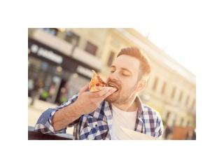 Muž pojídající pizzu ve městě